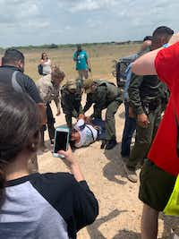 """<p><span style=""""font-size: 1em; background-color: transparent;"""">Dimmit County sheriff's deputies arrest a protester at the Carrizo Springs migrant children detention facility.</span></p>(Mitchell Velona)"""