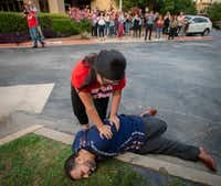 Angelica Andrade and Nicolas Hernandez of the North Texas Dream Team simulated an arrest in Dallas on June 26 for a group of volunteers who were undergoing training for rapid mobilization in case of immigration raids in the area.(Robert W. Hart/Special Contributor)