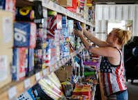 Dana Delgado restocks fireworks at Starr Fireworks in Kaufman County. Delgado has worked at the fireworks stand off and on for the past 10 years. (Vernon Bryant/Staff Photographer)