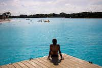 Thirteen-year-old Sachiko Steinhilper sits on one of the docks at the Crystal Lagoon at Windsong Ranch in Prosper on Tuesday.(Shaban Athuman/Staff Photographer)