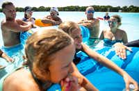 """Family and friends relax at the Crystal Lagoon at Windsong Ranch on Tuesday as they kick off their long Fourth of July holiday. Dave Finnigan (left) said, """"it's like the beach in your backyard.""""(Shaban Athuman/Staff Photographer)"""
