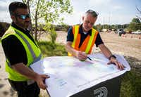 Tim Oliver (left), assistant director of Sanitation Services for the city of Dallas, and Kelly High, director of Sanitation Services, point out the hardest-hit areas of the city where debris needs to be collected at a temporary collection site near the intersection of  Highway 75 and Interstate 635 in Dallas on June 21.(Ashley Landis/Staff Photographer)