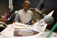 KKDA-AM (730) host Willis Johnson looks through a newspaper during a break on <i>The Willis Johnson Good Morning Show</i>&nbsp;in Grand Prairie in 2006.(File Photo&nbsp;/Tom Fox)