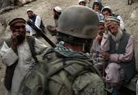 Village elders spoke with a U.S. Marine as Afghan forces search for weapons October 25, 2008 in the Korengal Valley of Kunar Province in eastern Afghanistan. Taliban insurgents enjoyed widespread public support in the contested valley, site of some of the heaviest fighting between U.S. forces and Taliban insurgents.(File Photo/Getty Images)