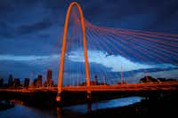 The setting sun illuminates the Margaret Hunt Hill Bridge and downtown Dallas after thunderstorms rolled through the middle of the Dallas-Fort Worth on Wednesday evening.(Tom Fox/Staff photographer)