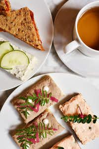 Sandwiches of ratatouille and Devonshire cheddar, and cucumber with cream cheese, mint and chives, top left, salmon rillette and capers, and duck confit with foie gras, bottom, and Moonlight Beauty Pu-erh tea.(Ben Torres/Special Contributor)