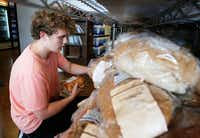 Volunteer Keegan Kasprowicz helped organize bread at Frisco Family Services Food Pantry on Thursday, July 11, 2019.(Vernon Bryant/Staff Photographer)