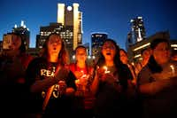 Denison, Texas friends (from center, left) Katy Schneider, Alison Earnhart and Kathia Suarez, chant with hundreds of others during the Lights for Liberty candlelight vigil outside Dallas City Hall, Friday evening, July 12, 2019. The group says they want to shine a light on the horrific abuses of the Trump administration in detention centers at the southern border, points of entry and across the country.(Tom Fox/Staff photographer)