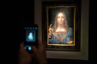 A visitor took a photo of the painting <i>Salvator Mundi</i> by Leonardo da Vinci at Christie's New York Auction House in November 2017 in New York City.&nbsp;(Drew Angerer/Getty Images)