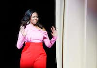 Former first lady Michelle Obama waves to the crowd as she makes her way on the stage during an interview promoting her memoir&nbsp;<i>Becoming </i>at American Airlines Center on Dec. 17, 2018.(Vernon Bryant/Staff Photographer)