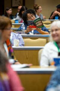 An attendee of the Mayborn Literary Nonfiction Conference flips through the program of events from her seat in the audience.<br>(Hatch Visuals/Kara Dry<br>)