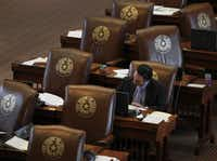 In this 2013 photo, State Rep. Terry Canales, D-Edinburg, works at his House desk in the Capitol. He passed a bill this year that set up tougher penalties for fakers who change the display on Caller ID before making illegal telemarketing and scam calls.(Louis DeLuca/Staff Photographer)