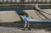 Officials survey the spillway at White Rock Lake on Thursday, July 25, 2019 in Dallas.(Ryan Michaelesko/Staff Photographer)