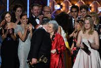 The cast and crew of <i>The Handmaid's Tale</i> accept the award for Outstanding Drama Series during the 69th Emmy Awards at the Microsoft Theatre on Sept. 17, 2017, in Los Angeles. In red is author Margaret Atwood, whose novel the show is based on.(Frederic J. Brown/Agence France Presse)