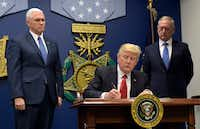 <p>President Donald Trump&nbsp; signed an executive action on extreme vetting at the Pentagon in Washington on Jan. 27, 2017, flanked by Vice President Mike Pence (left) and Defense Secretary James Mattis, who resigned in December 2018.</p>(Susan Walsh&nbsp;/The Associated Press)