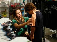 Melanie Davis looks to see if a shirt fits as she puts it on her son, Hudson Davis 6 as they shop for back to school clothes at J.C. Penney inside Stonebriar Mall in Frisco, Texas on Wednesday, July 24, 2019. (Vernon Bryant/The Dallas Morning News)(Vernon Bryant/Staff Photographer)