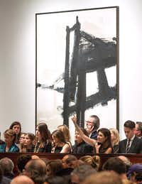 Dallas-based Capera Ryan (lower right, with hand up), Deputy Chairman of Christie's, takes a bid by telephone in the sale room at Christie's in New York.(Christie's)