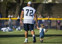 Dallas Cowboys center Travis Frederick (72) walks with his daughter after an afternoon practice at training camp in Oxnard, Calif., on July 29, 2019.(Ashley Landis/Staff Photographer)