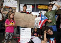 About 200 to 300 people from the Dallas-Fort Worth area Puerto Rican community, including Maria de los Angeles Cruz Lopez (second from left) and her kids Maia Sofia Bonet Cruz (left) and Laila Isabel Bonet Cruz (seated, center right), came to protest Gov. Ricardo Rossello outside the Adobo Puerto Rican Cafe in Irving, Texas, on July 21, 2019. People are upset about the Puerto Rican governor's leaked, offensive online messages and want him to resign.(Tom Fox/Staff photographer)