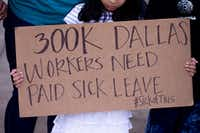 A  girl held a sign during during a news conference about a paid sick time ordinance outside of the Dallas City Hall on June 20, 2019.(Shaban Athuman/Staff Photographer)
