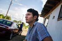 Francisco Galicia waits outside his family's home as a television journalist sets up a camera and lights in the family's living room.(Ryan Michalesko/Staff Photographer)