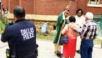 """<p>Deacon Roberto Alvarez and Raul Rodriguez bless a couple with holy water Sunday as Dallas police Officer Anthony Colon watches at the&nbsp;<span style=""""font-size: 1em; background-color: transparent;"""">Cathedral Shrine of the Virgin of Guadalupe. Extra security measures were in place at the church a day after a massacre at a Walmart in El Paso.</span></p>(Tommy Noel/Staff photographer)"""