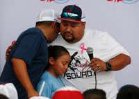Ray Garcia (left) of El Paso hugs Danny Latin (in white facing left) and his daughter at the end of the candlelight vigil at The Sportspark in El Paso, Texas on Sunday, August 4, 2019. (Vernon Bryant/Staff Photographer)