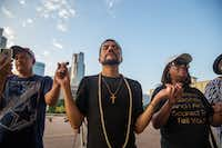 El Paso native Jaime Morales (center) sings with Abel Lopez (left) and Eva Miles (right) as they gather to honor the victims of Saturday's mass shooting in El Paso during a candlelight vigil outside Dallas City Hall in Dallas on Sunday, Aug. 4, 2019.(Lynda M. Gonzalez/Staff Photographer)