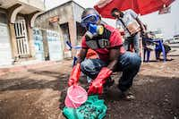 A health worker wearing protective gear mixed water and chlorine in Goma, Congo, in July.(Pamela Tulizo/Agence France-Presse/Getty Images)
