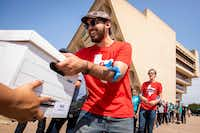Michael Gonzalez, of the Democratic Socialists of America, helps unload a truckload of boxes as a coalition of labor and faith groups and political activists delivers petitions to at City Hall calling for a city ordinance mandating paid sick time to be placed on the November ballot on Monday, June 11, 2018, in Dallas.(Smiley N. Pool/Staff Photographer)