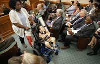 Mesquite mother Linda Badawo (left) pushed her medically fragile son, D'ashon Morris, past representives of Superior HealthPlan (seated right), the Texas subsidiary of health care giant Centene, after she testified before the Texas House Committee General Investigating and Ethics in June 2018. Badawo is suing Superior HealthPlan in a case tied up in the state appeals court, where the company argues that Badawo and D'ashon are suppressing its free speech rights.(Tom Fox/Staff Photographer)