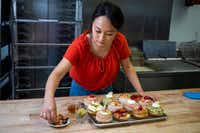 Jinny Cho, owner of Detour Doughnuts and Coffee, puts finishing touches on an assortment of doughnuts at Detour Doughnuts and Coffee in Frisco.(Shaban Athuman/Staff Photographer)