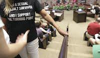 """A person wearing a t-shirt saying """"I am a sexual assault survivor"""" waits to speaks in support of The Turning Point rape crisis center, during the Plano City Council meeting on Monday, Aug. 12, 2019 in Plano, Texas.(Jason Janik/Special contributor)"""