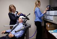 Lab manager Ellen Morris adjusts a rTMS (repetitive Transcranial Magnetic Stimulation) device on research assistant Justin Jacqmain as fellow assistant Rachel O'Hair reads them on the main unit at UT-Dallas' Brain and Behavioral Sciences Department in the hospital district of Dallas. Forty Veterans Administration hospitals have been using this procedure for years to treat depression and obsessive compulsive disorder.(Tom Fox/Staff Photographer)