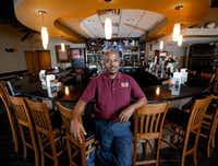 Kassahun Kebede, an immigrant from Ethiopia, stands in his restaurant, Yenat Guada Ethiopian Cuisine, on Aug. 9, 2019.(Brandon Wade/Special Contributor)