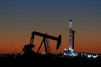 <p>An oil rig and pump jack in Midland. Falling natural gas prices have been unkind to Texas, forcing some producers to rethink their drilling plans and lay off workers.</p><p></p>(Jacob Ford/The Associated Press)