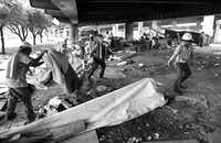 Street Dept. workers for the City of Dallas take apart the shanty town under the I-45 overpass near downtown Dallas, one afternoon in June 1994. The homeless residents were given an hour to vacate the premises that morning. (Erich Schlegel/The Dallas Morning News)
