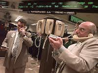 New York Stock Exchange trader Peter Tuchman, right, and others talk at a phone post, Monday, Nov. 16, 1998. Stocks rose Monday, briefly lifting the Dow back above 9,000, as the global backdrop improved with a new Japanese stimulus plan and a resolution to the latest Iraqi crisis.