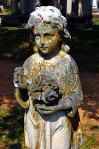 The figure of one of two daughters who died in childhood stands on the grave site of the Basham family in Mount Holly Cemetery in Little Rock, Ark.