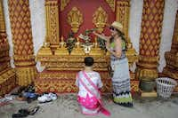 Kay Sayprasits (right) sprays water on statues of Buddha as Nikki Thommasouk prays in front of them. Members of the temple follow Theravada, which is widely regarded as the oldest surviving school of Buddhism, and is practiced in Southeast Asia.Matthew Busch - Staff Photographer