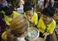 Members of the Women's Lao Community of Dallas and Fort Worth Phommachack Seng, (from left), Hongthong Vinaithong and Methy Kittirath pray and offer donations.Matthew Busch - Staff Photographer