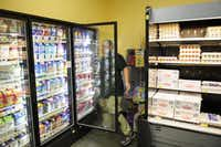 Orlando Guajardo rearranges items in the display refrigerators at the Wal-Mart store off Greenville. Trader Joe's, Sprouts Farmers Market and WinCo Foods have put pressure on Wal-Mart, Kroger, Tom Thumb and Target.( Matthew Busch  -  Staff Photographer )