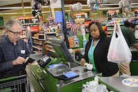 Marvin Stone pays for his groceries as cashier Netanya Christian bags up his purchases at the Wal-Mart Neighborhood Market off Greenville in Dallas.( Matthew Busch  -  Staff Photographer )