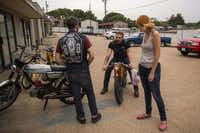 Josh Lacheney, center, returns from ordering food at Tacos La Banqueta Puro, a club tradition, which is just across the street from Kyle's Scooter Shop, in Dallas, before a weekly Pine Box Pedal Club ride. With him are Katie Arterburn, right, and Oliver Sitrin.( Brittany Sowacke  -  Staff Photographer )