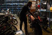 "Josh Lacheney, of Dallas, wheels his motorcycle out of Kyle's Scooter Shop on July 14, 2014. Although the shop specializes in scooters and mopeds, owner, Kyle Salter, says he can fix ""anything with two wheels.""( Brittany Sowacke  -  Staff Photographer )"