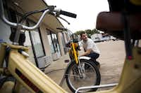 Roger Thompson, of Flower Mound, Texas, sits next to his moped outside of Kyle's Scooter Shop in Dallas.( Brittany Sowacke  -  Staff Photographer )