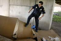 Dallas Police Officer Robert Garcia stomps down a homeless shanty under I-45 and Louise near downtown Dallas, in January 2005. Dallas Police rousted the homeless people living in the area and cleared them out before TxDOT came in and bulldozed their shanties and hauled them away. (Lara Solt/The Dallas Morning News)
