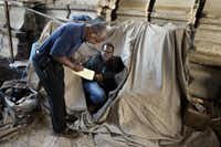 Michael Culpepper, right, gathers a few posessions from his camp under Interstate 45 before going with Winford Cross to Homeward Bound detox in March, 2009. (Courtney Perry/The Dallas Morning News)