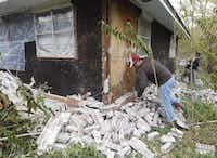 Chad Devereaux cleaned up bricks after two earthquakes struck in Sparks, Okla., in November 2011. Oklahoma's geological survey is currently working with energy companies to map faults across that state.(2011 File Photo  -  The Associated Press )