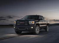 The 2014 GMC Sierra All Terrain front three quarter view at dusk shows the projector beam headlamps with signature LED lights.